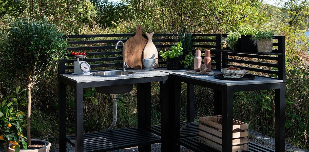 Bellac utekjøkken, sort med kjøkkenutstyr og ferske krydderplanter og grønne planter i store og små potter