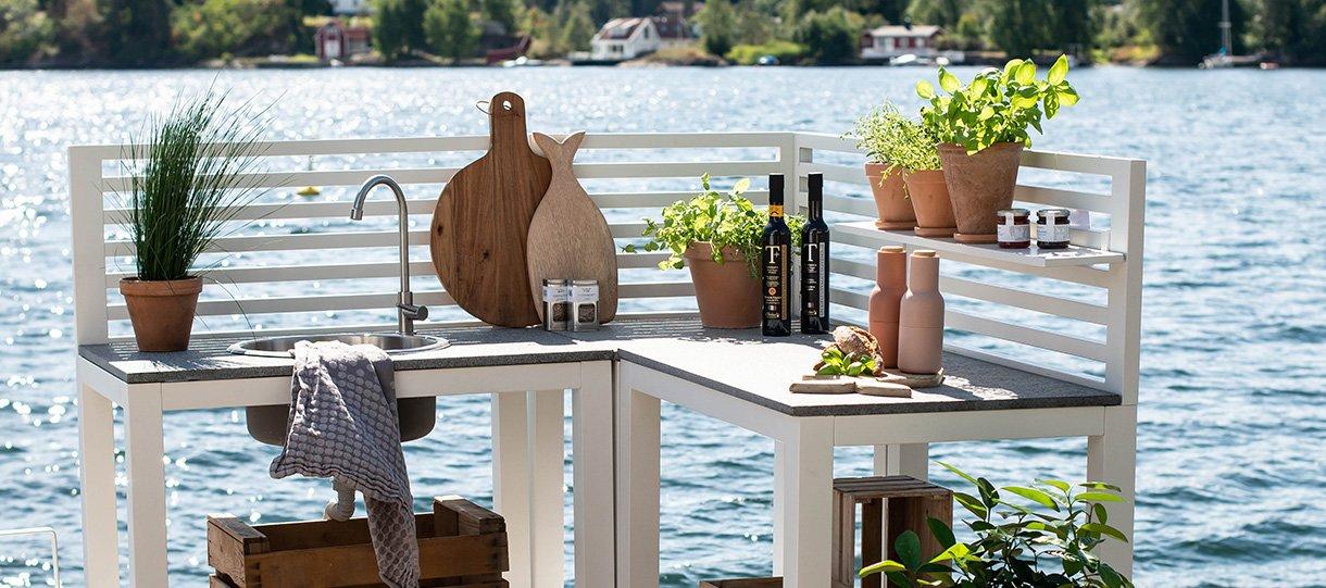 Bellac utekjøkken, hvit med kjøkkenutstyr og ferske krydderurter i små potter på kjøkkenbenken