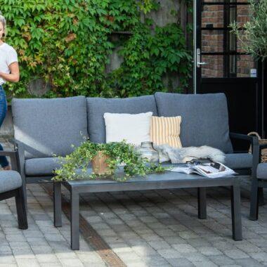 Moderne sittegruppe i aluminium, skylar sort, sofa, stoler, bord og puter på veranda