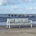 Belfort sofa med hvit aluminiumramme og grå puter ligger på stranden ved havet.