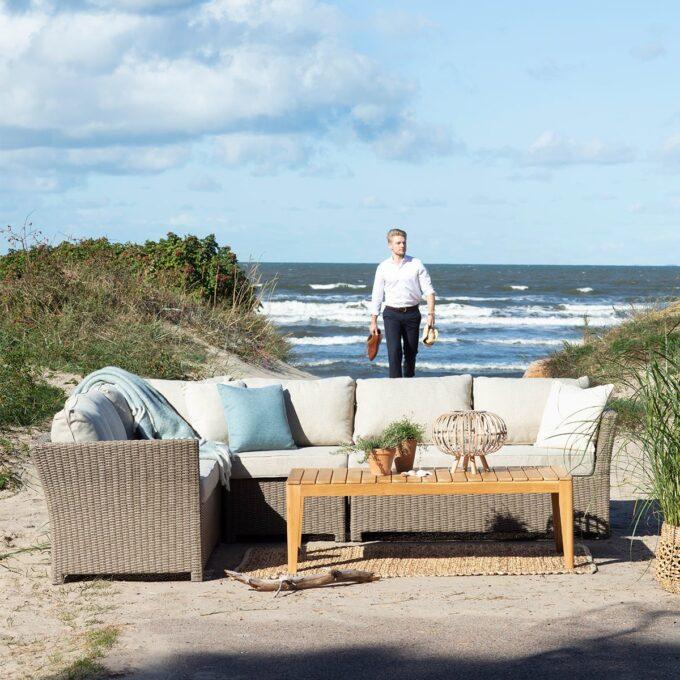 Modulgruppe Adams i grå kunstrotting med sofabord Adams i teak på stranda med mann og hav i bakgrunn