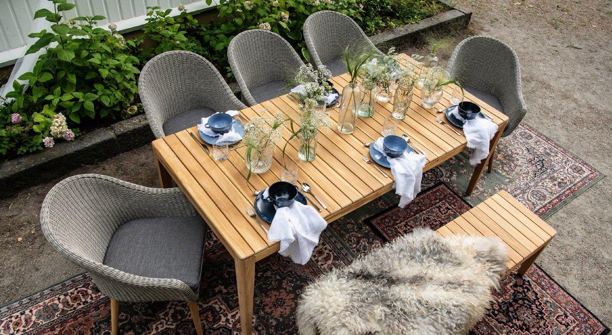 Sitteplass ved husveggen møblert med utestoler i kunstrotting, trebord og trebenk