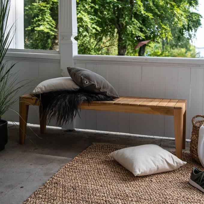 Agios benk i teak med puter på veranda