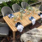 Oppdekket spisebord Agios i helteak og hagestoler stående på tepper på uteplassen