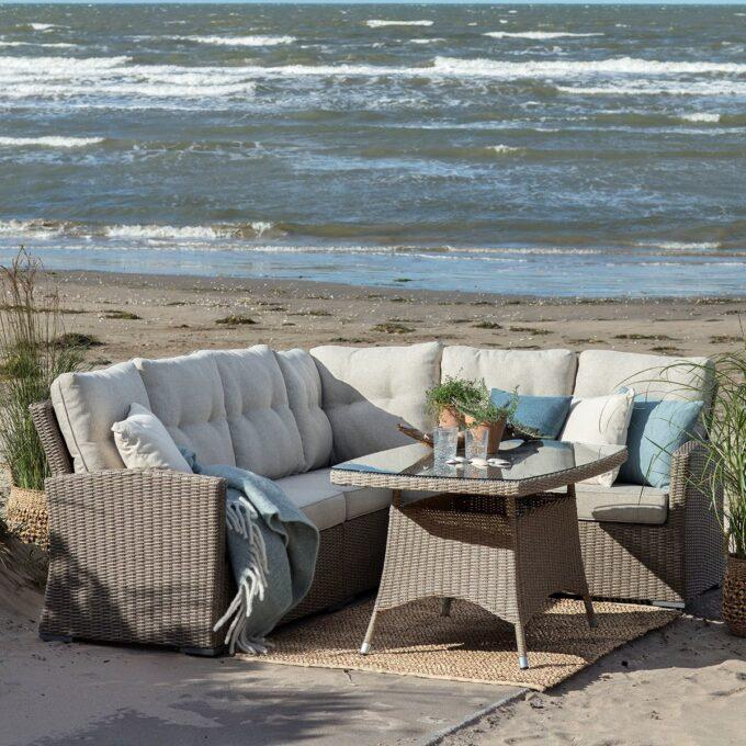 Stor sofagruppe Ashfield i naturfarget kunstrotting med sofabord på strand med hav i bakgrunn