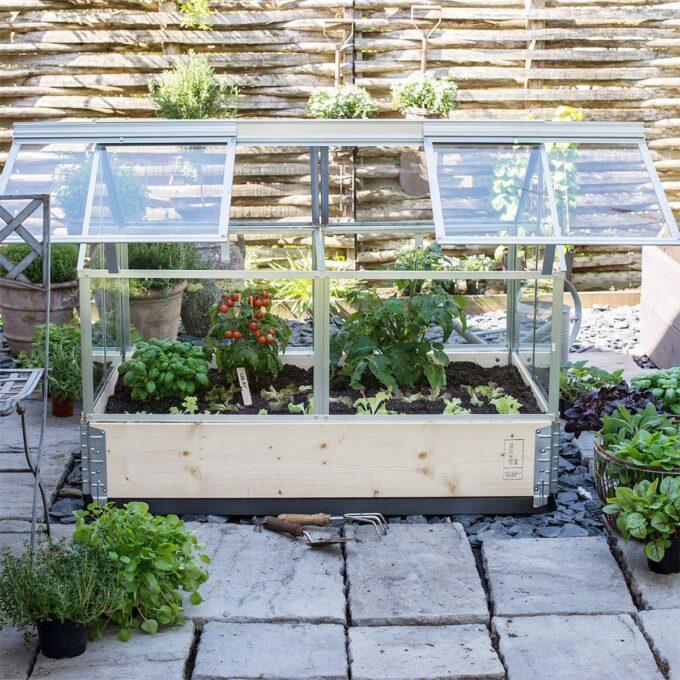 Gaia balkongdrivhus med tomater, salat og krydderurter - der taket er løftet til side