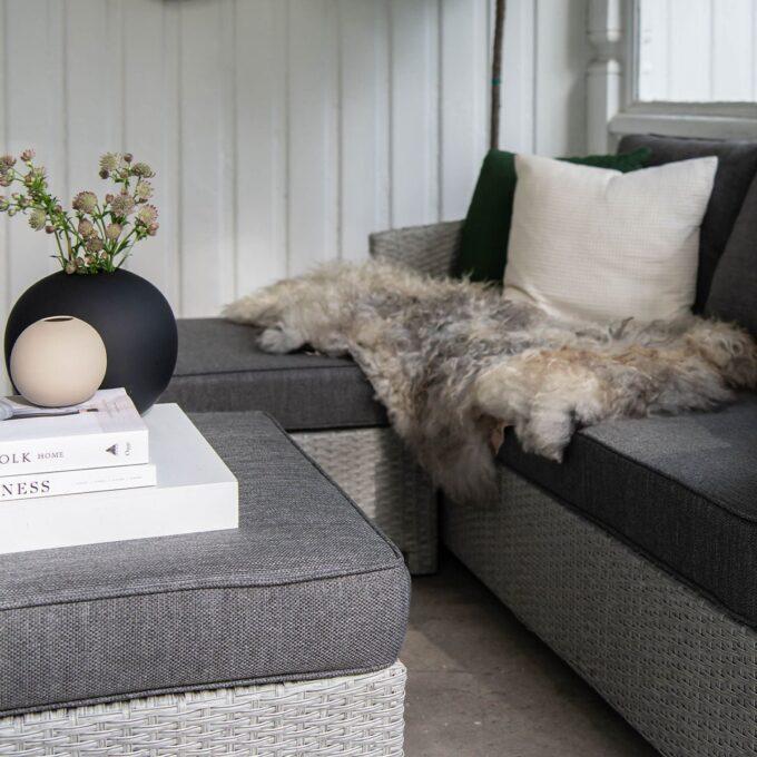 Nærbilde av sofagruppe Conmay - hjørnedel i lysgrå kunstrotting på veranda