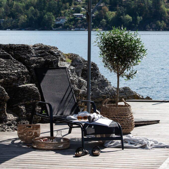 Solseng Creston i sort matt aluminium med stor plante i potte på terrasse ved havet