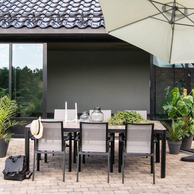 Spisegruppe Dakota i sort matt aluminum med hengeparasoll og grønne planter i krukker på terrasse