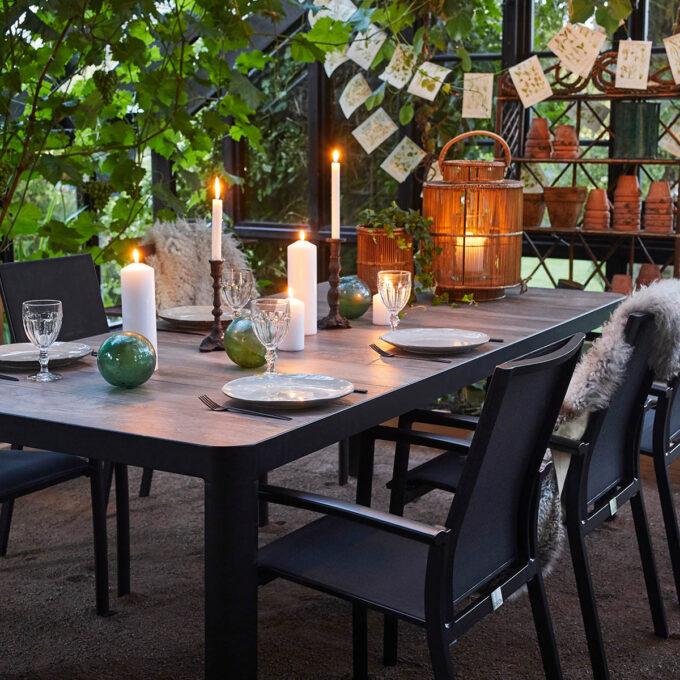 Nydelig spisegruppe med flott keramisk bordtopp og sorte stablebare spisestoler.