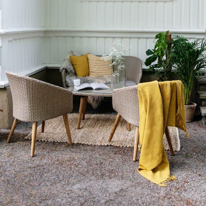 Sofagruppe Danvers i naturfarget kunstrotting på uteteppe hamp med grønne planter i utepotter