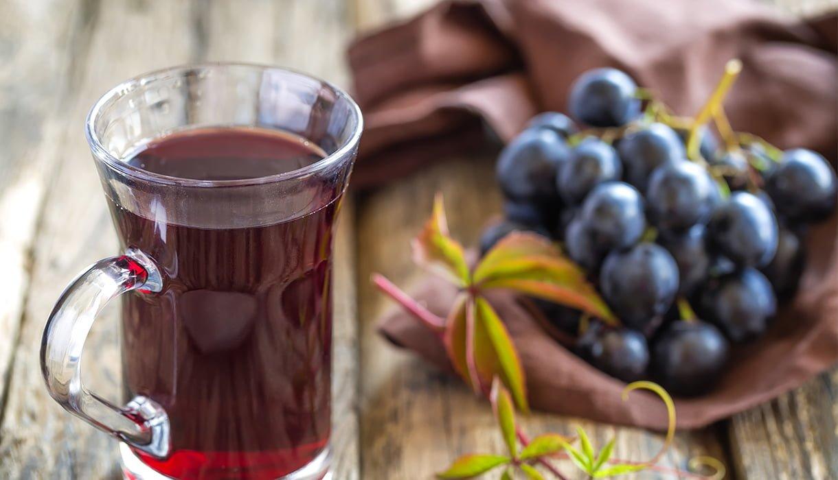 glass med druesaft og blå druer på trebord