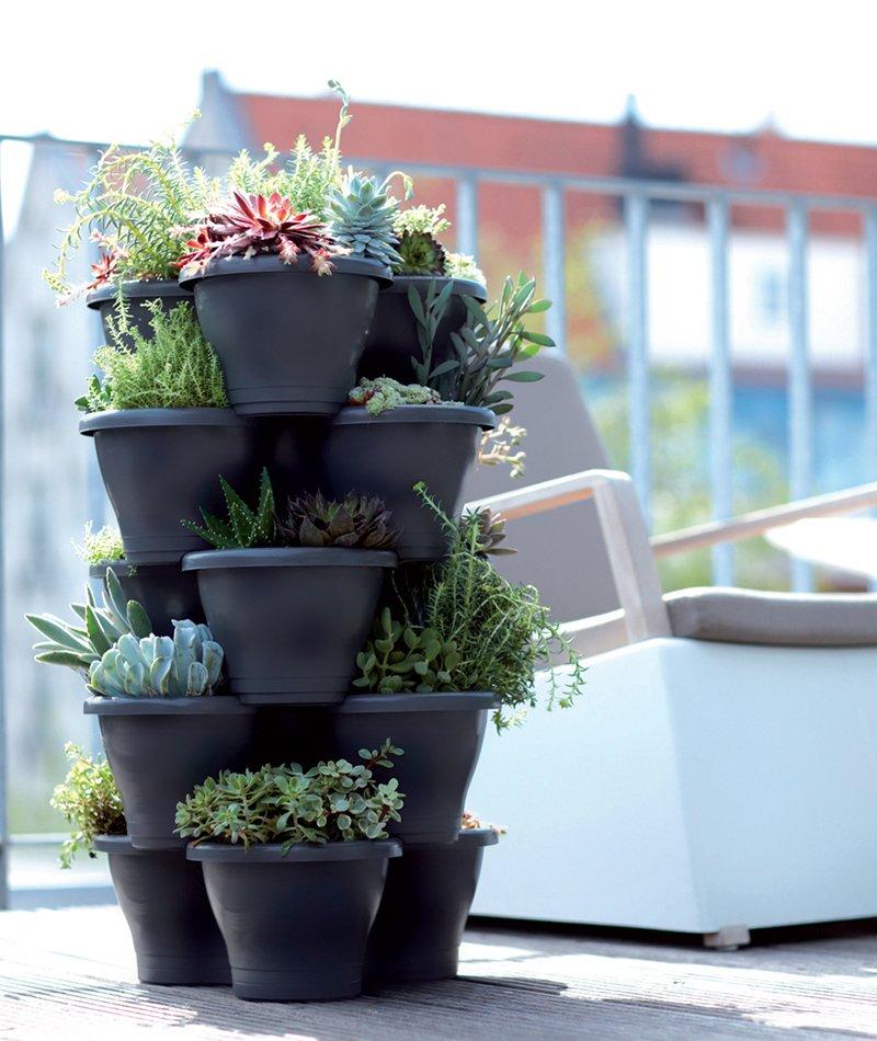 Et tårn av stablede Elho utepotter i plast med planter