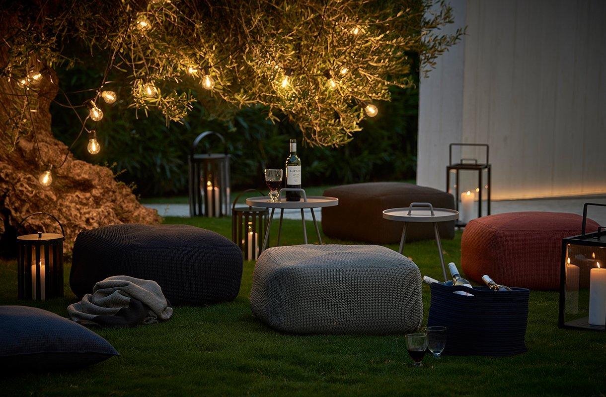 Kveld i hagen, med lyslenker i trærne og et utvalg cane line-produkter som sittepuffer og bord