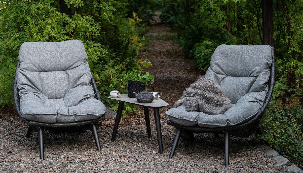 Hvilestoler med grå puter og sidebord i aluminium med keramikkplate