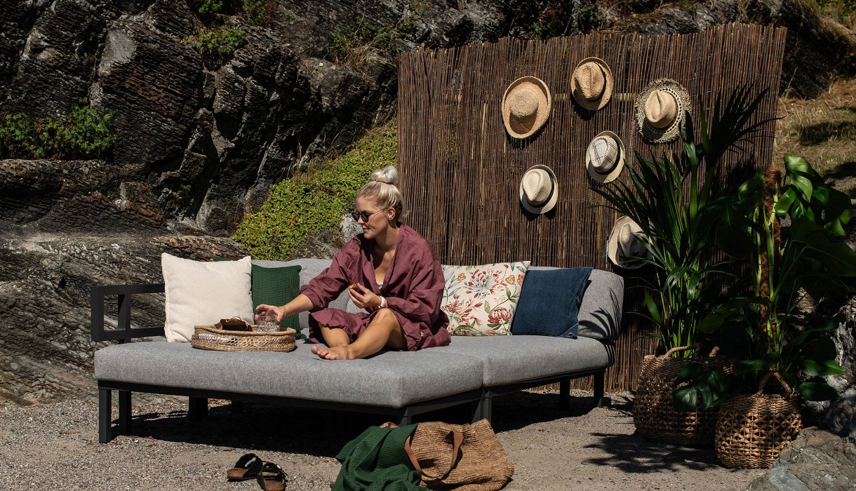 Kvinne slapper av i Gonesse loungegruppe, sofaseng og daybed i aluminium på uteplassen