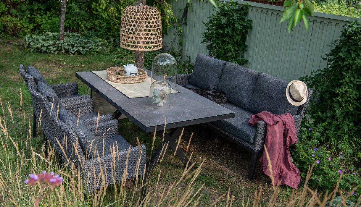 Spisegruppe Hammel mørkgrå kunstrotting, hagestoler og hagesofa med keramikkplate, hagebelysning og grønne hageplanter