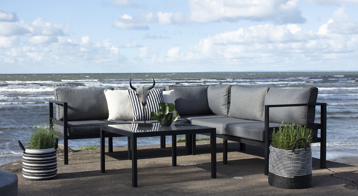 Hjørnegruppe Joliette med sofa i sort aluminium og bord med glassplate på platting ved havet