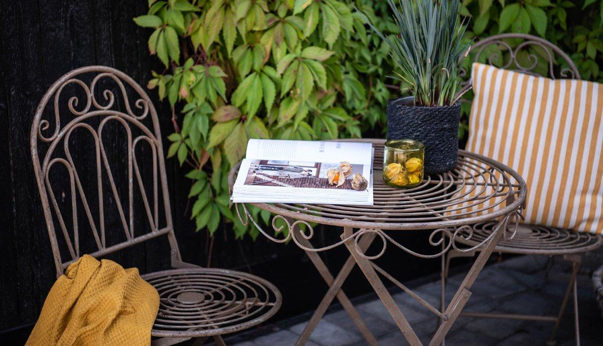Hagemøbler uterom Kafésett stol bord stål antikk planter pute pledd violetta