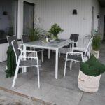 Spisestoler og oppdekket spisebord Mendoza i matt hvit aluminium med grønn teppe og puter på uteplass