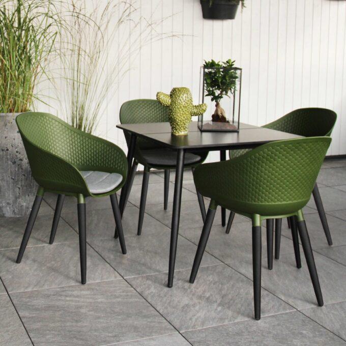 Spisestoler Pasa i grønn/eucaluptys og spisebord på terrasse med hvit trevegg i bakgrunn og grønne planter i krukker