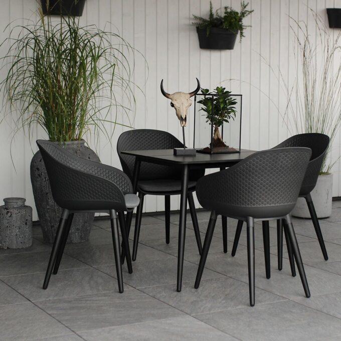 Spisestoler Pasa i grå/sort og spisebord på terrasse med hvit trevegg i bakgrunn og grønne planter i krukker