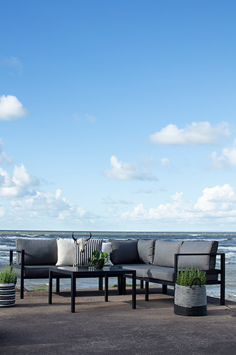 Joliette sofagruppe med bord og hjørnesofa på platting med havet i bakgrunn