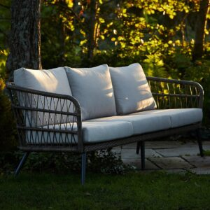 Nydelig 3 seters sofa i naturfarget kunstrotting. fletten på kunstrottingen og de lyse putene gir et romantisk, stramt utrykk
