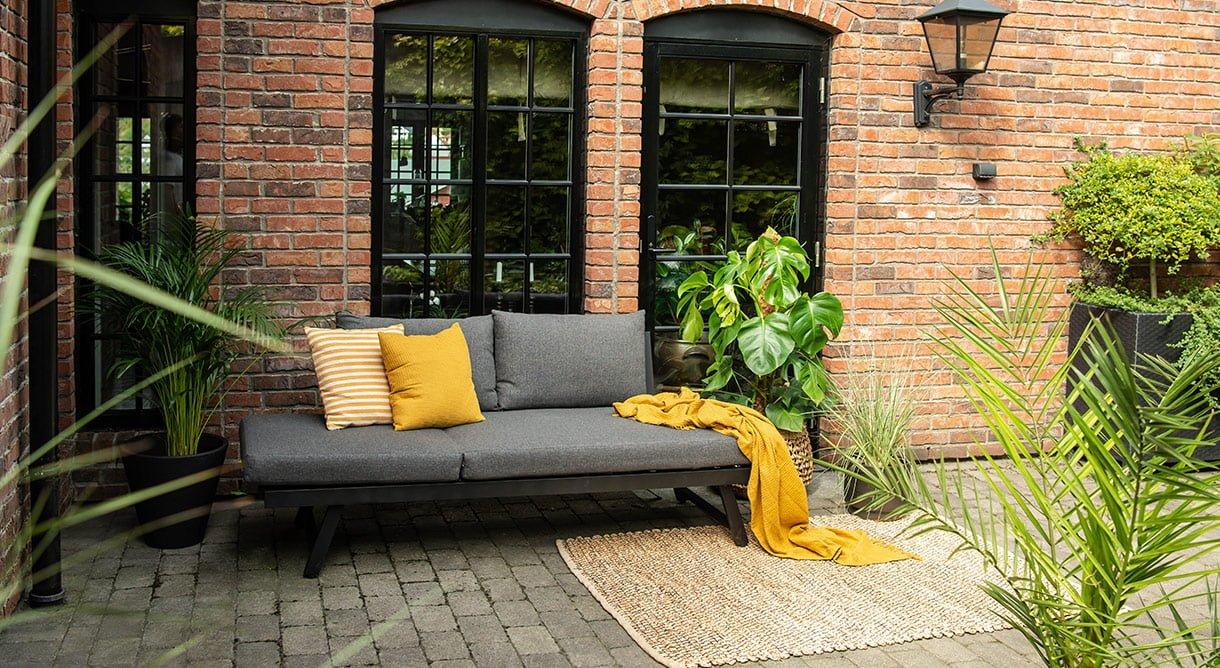 Solstol som kan gjøres om til sofa - på uteplass foran mursteinsvegg