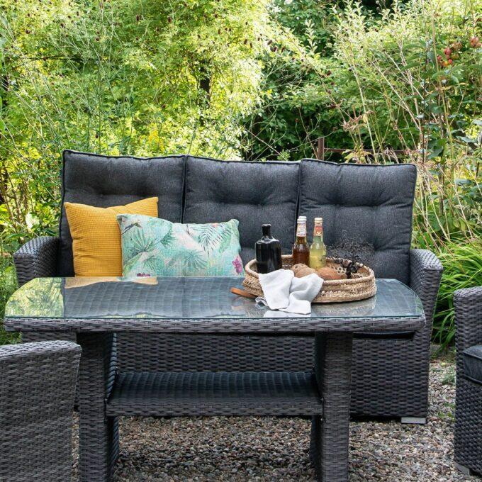 Sofa 3-seter Nyborg i mørkgrå kunstrotting med hagebord i grønn hage