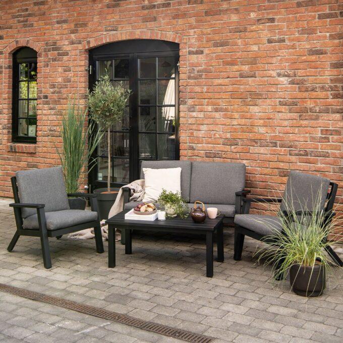 Sofagruppe Orbit i sort aluminium med store, grønne planter i potter på terrasse