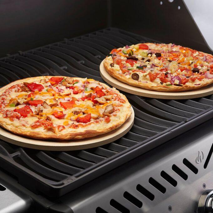 Pizzasteiner på grill med ferdige pizzaer på