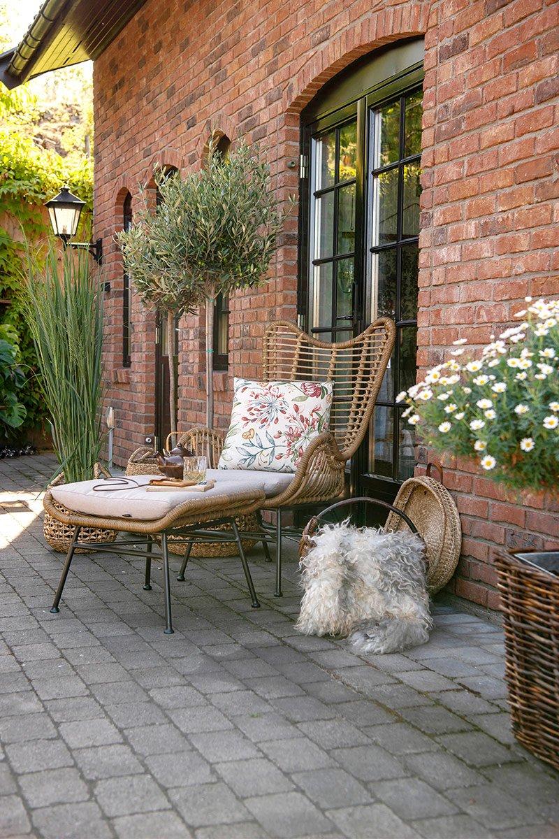 Rigel hvilestol i naturlig materiale på uteplass foran mursteinsvegg
