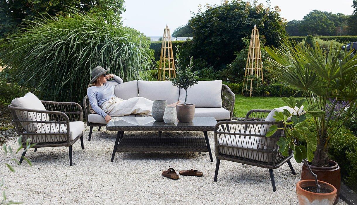 Nydelig sofagruppe i naturfarget kunstrotting. fletten på kunstrottingen og de lyse putene gir et romantisk, stramt utrykk