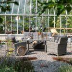 Sofagruppe Anholt, 3-seter sofa, stoler og sofabord i grå kunstrotting i solfylt hage