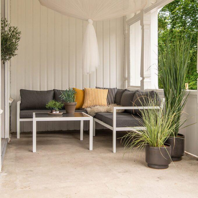 Hjørnegruppe Joliette og sofabord i hvit aluminium på terrasse med palmer i store og små potter