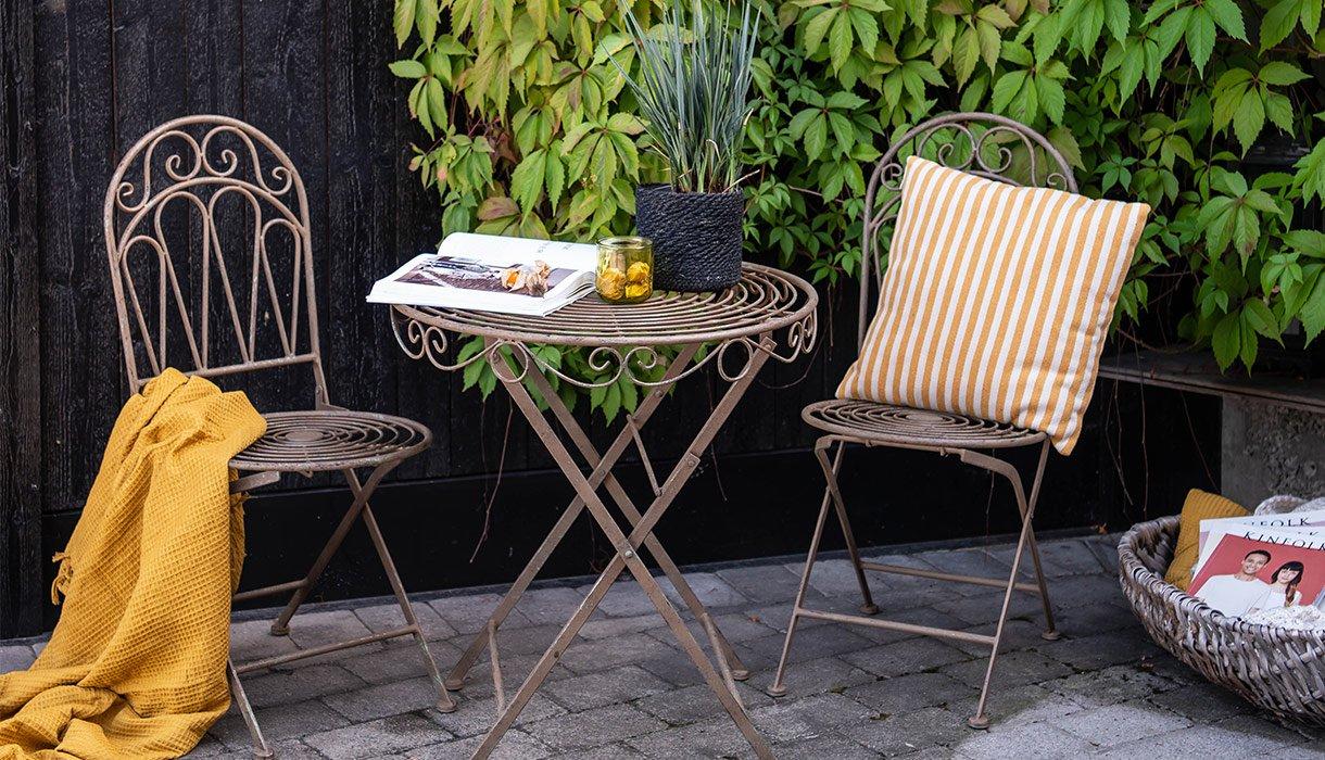Elegant Viola cafesett bestående av to stoler og bord foran brunbeiset vegg