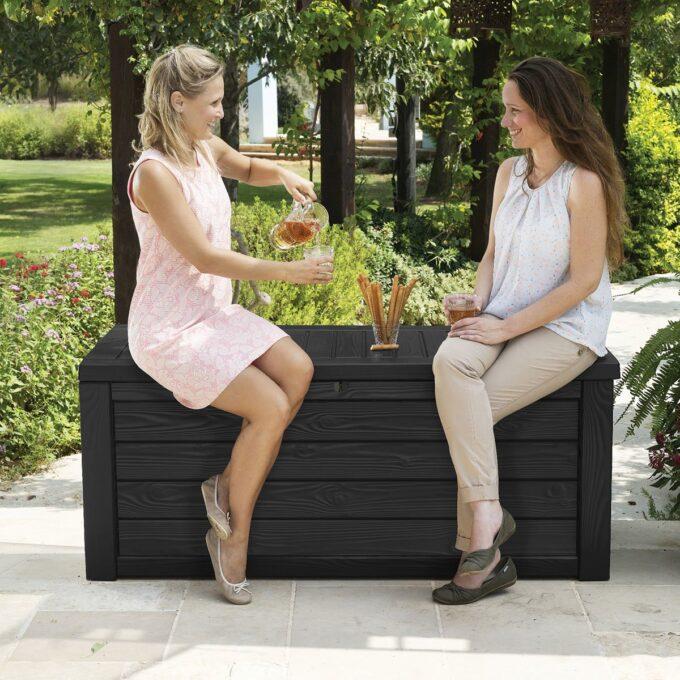 to personer sitter og koser seg med drikke og snacks på putekasse