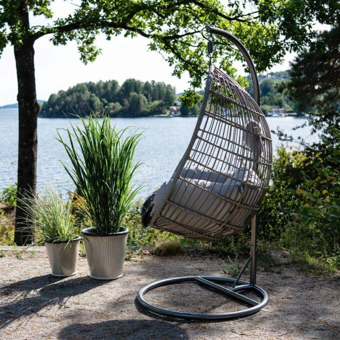 Henge stol for utendørs i grå kunstrotting og aluminumsramme. Grå puter i olefinstoff.