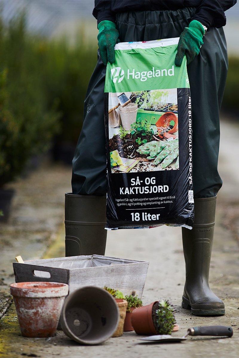 gartner holder stor pose med jord i drivhus