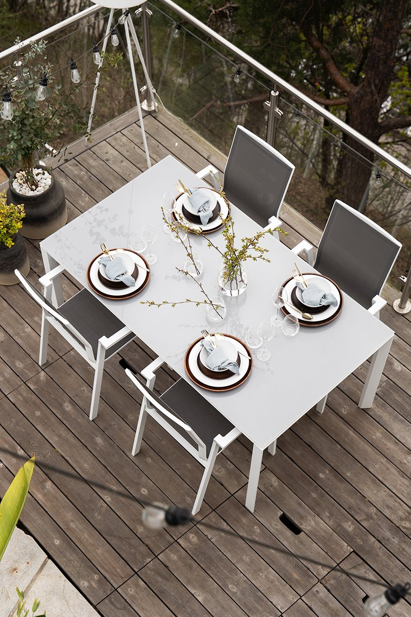 Et hagerom for daglig kos - langt spisebord i lett og lys aluminium, og spisestolene med ermelener