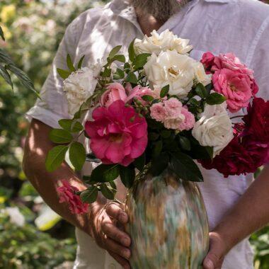 Røde, hvite, rosa roser av diverse sorter i en vase.