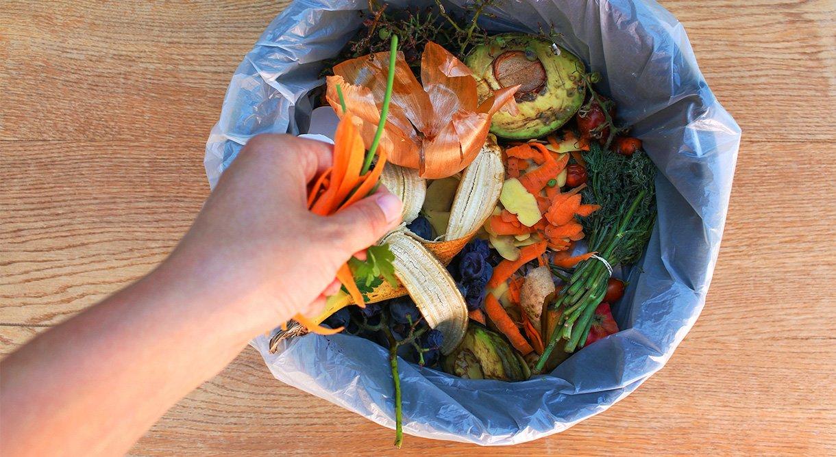 hånd som kaster mat i avfallsbøtte