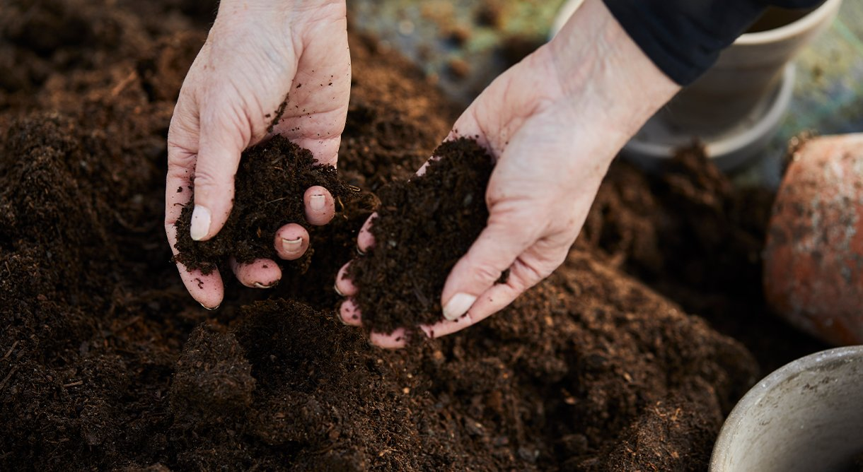 hender som og holder kompost-jord
