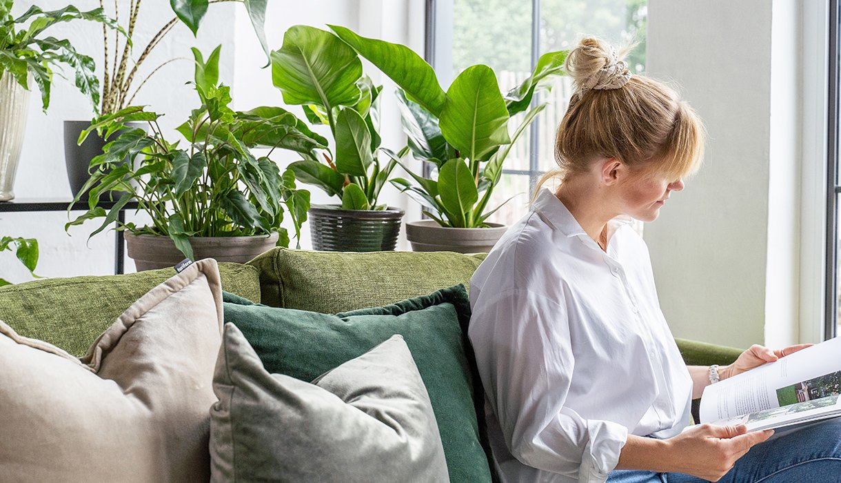 kvinne sitter i grønn sofa med store puter og leser magasin. Mange grønne planter i bakgrunnen.