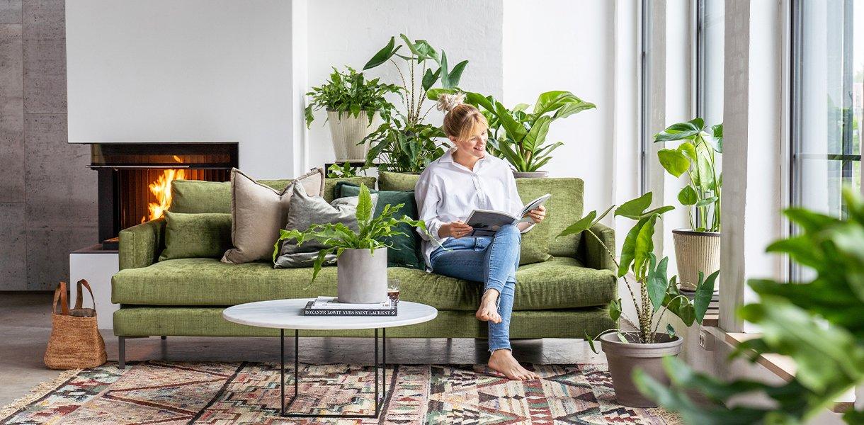 stue-interiør med masse grønne planter. kvinne sitter i sofa og leser