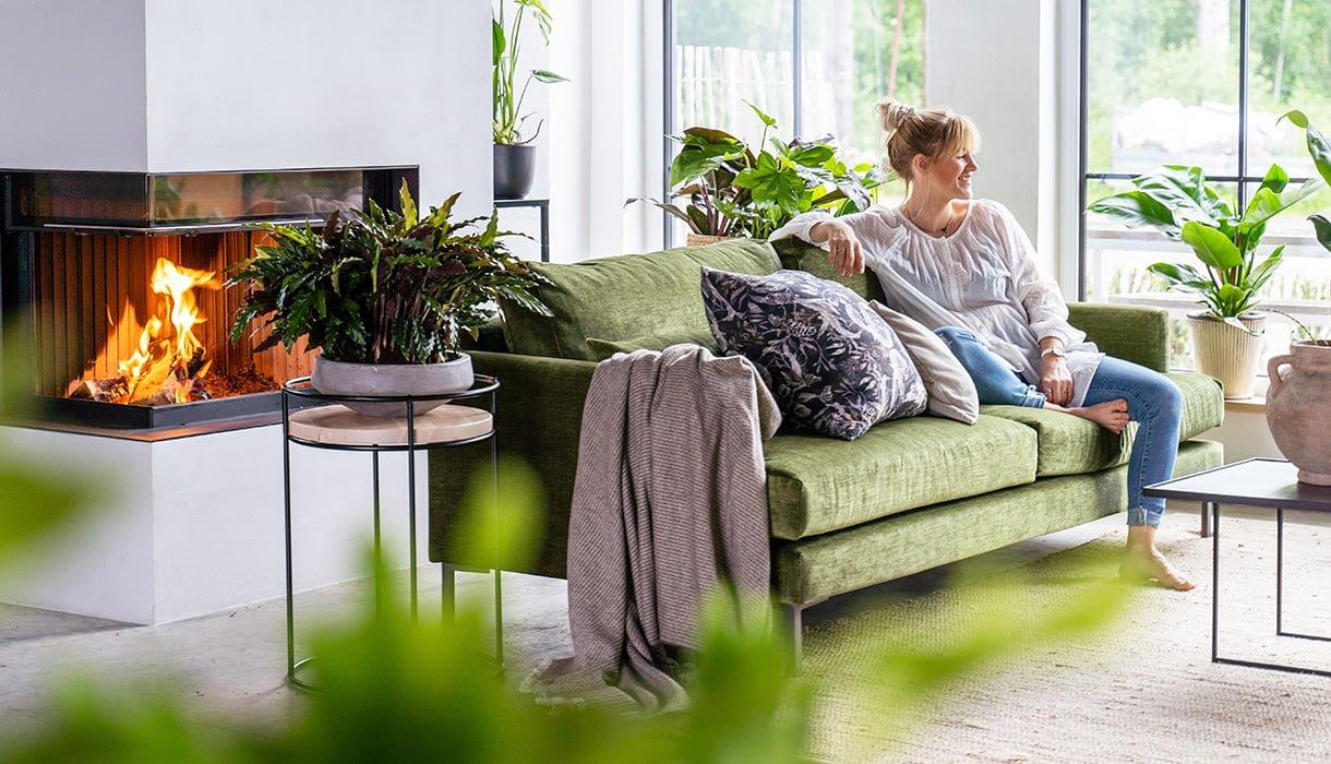 stueinteriør med peis, grønn sofa og masse grønne planter