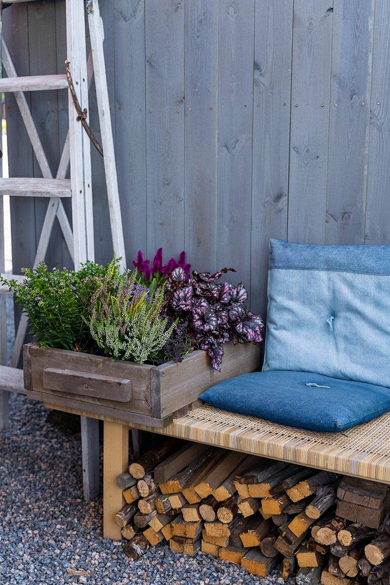 benk med puter og kasse med høstplanter , lyng