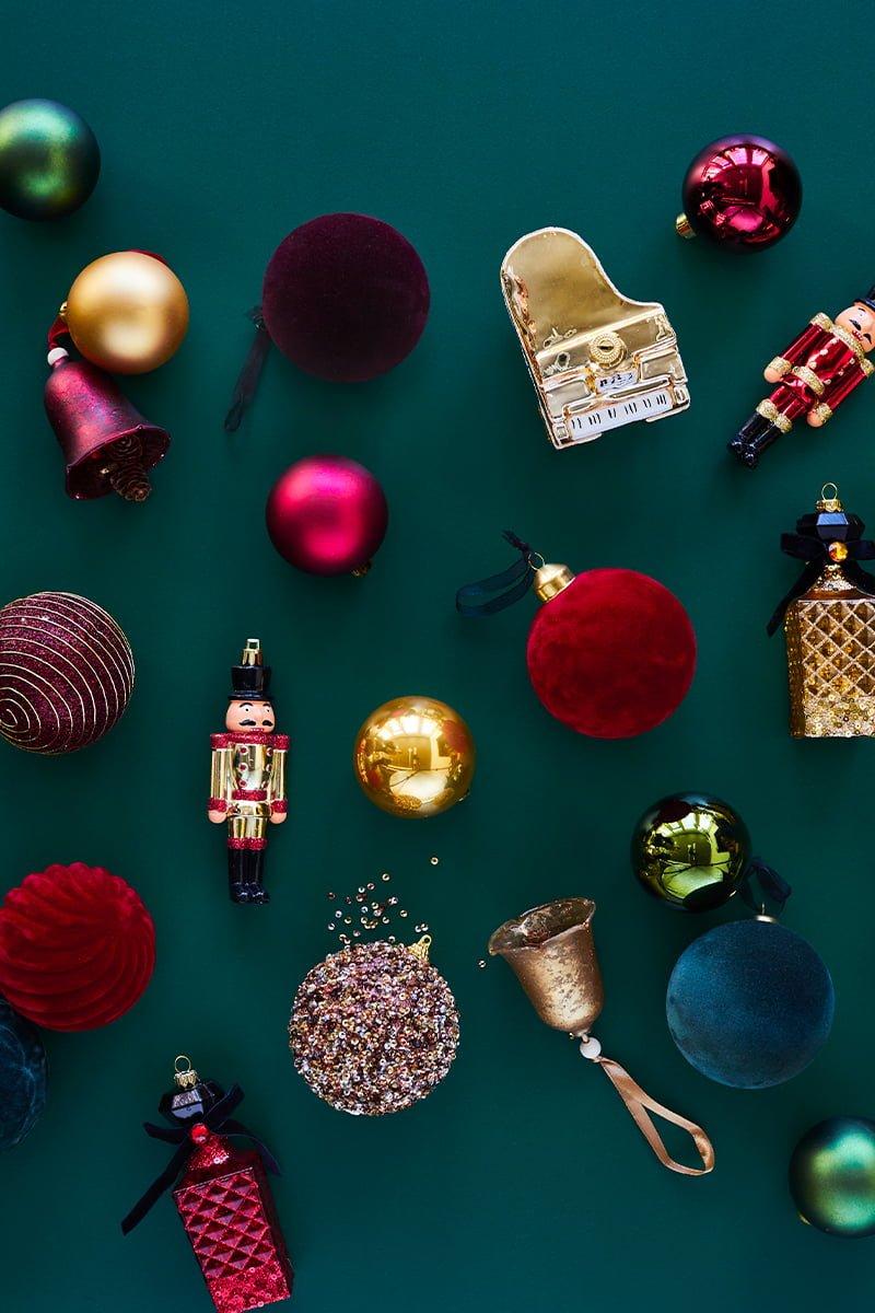 Masse forskjellig elegant juletrepynt på grønn bakgrunn