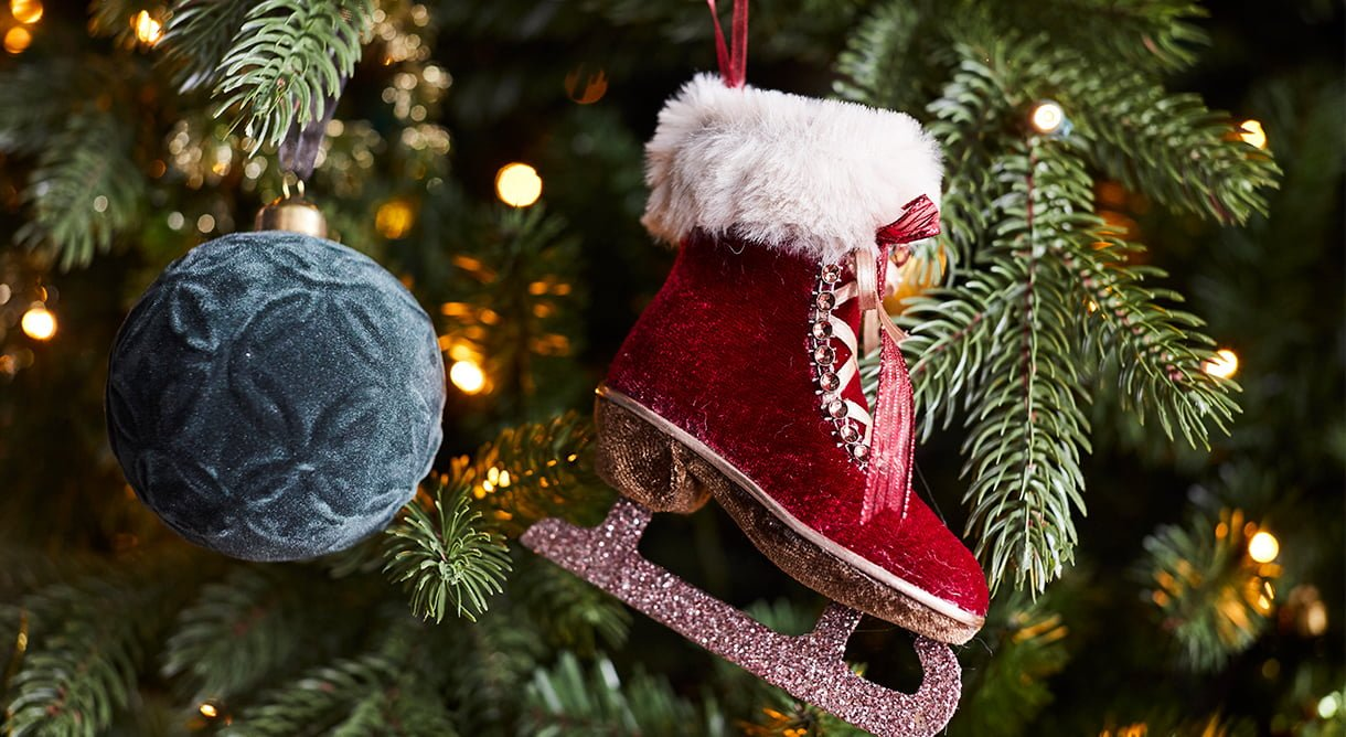 nærbilde av juletre med juletrepynt. Grønn kule i fløyel og rød skøyte i fløyel.